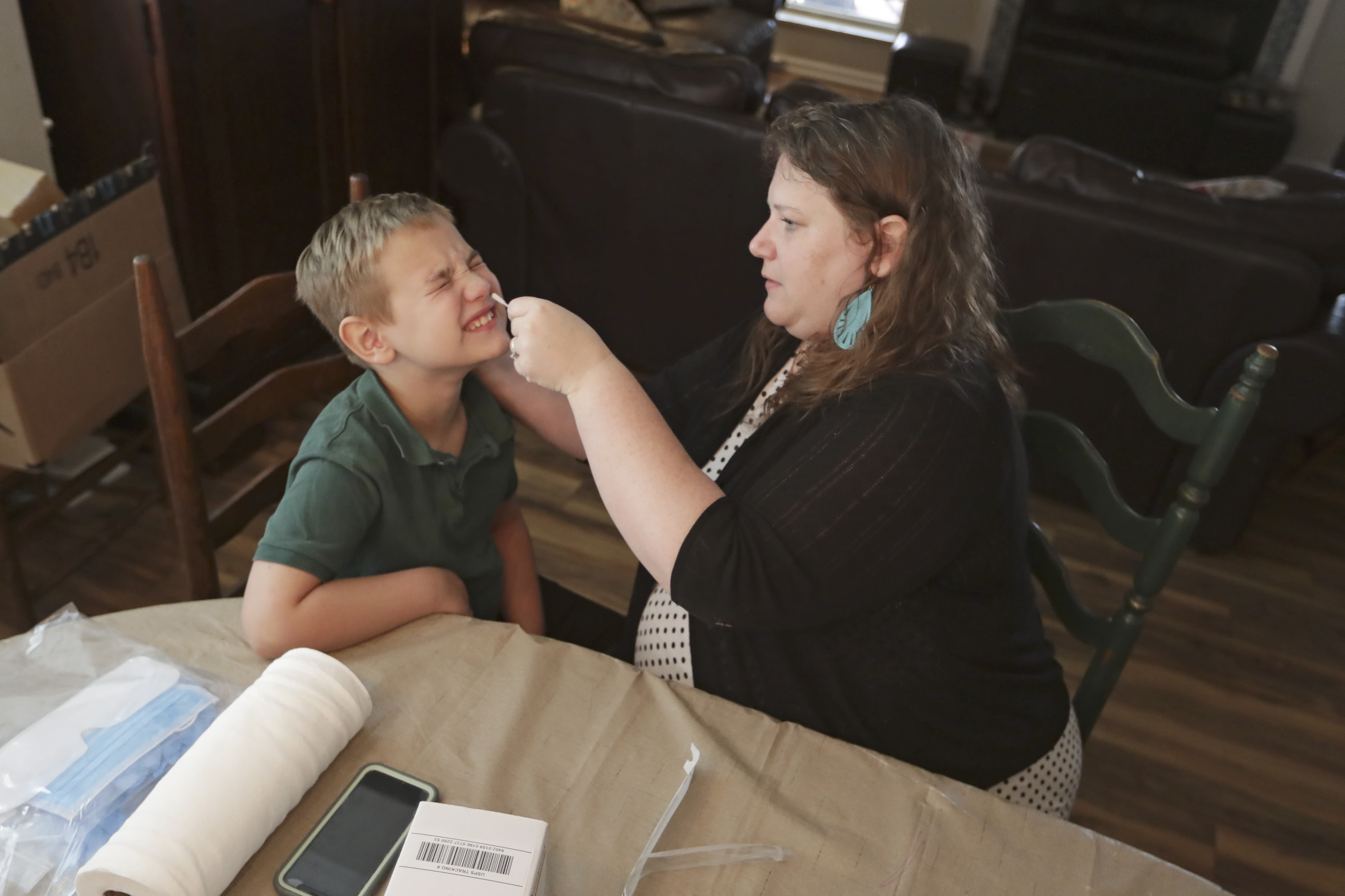 Mendy McNulty swabs the nose of her son, Andrew, 7, Tuesday, July 28, 2020, in their home in Mount Juliet, Tenn. Six thousand U.S. parents and kids are swabbing their noses twice a week to answer some of the most vexing mysteries about the coronavirus. The answers could help determine the safety of in-class education during the pandemic. (AP Photo/Mark Humphrey)
