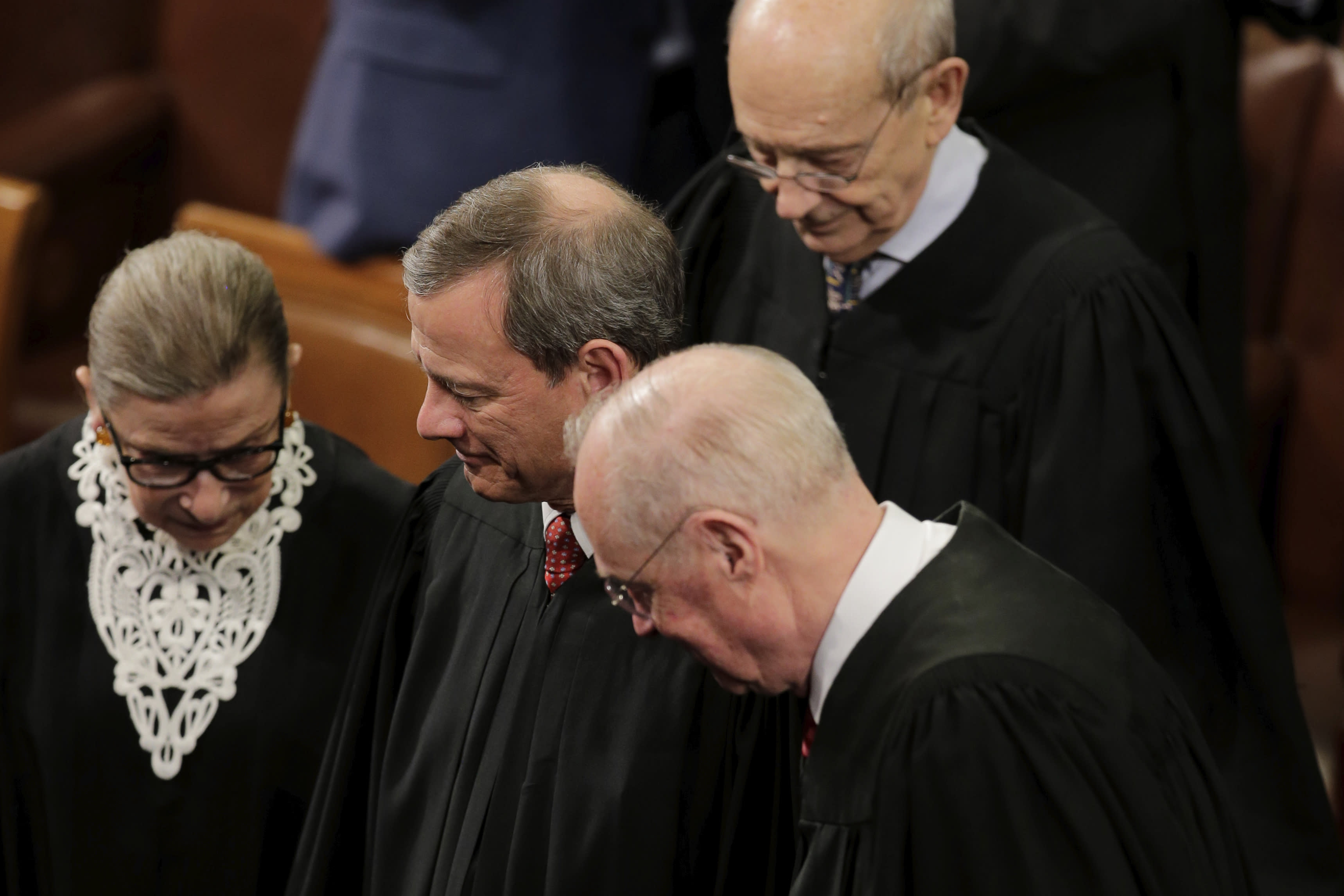 FILE - In this Jan. 12, 2016, file photo, Supreme Court Justices, from left, Ruth Bader Ginsburg, Chief Justice John Roberts, Anthony Kennedy and Stephen Breyer arrive on Capitol Hill in Washington, for President Barack Obama's State of the Union address before a joint session of Congress. Ginsburg didn't put on her judge's robe without also fastening something around her neck. Ginsburg called her neckwear collars, or jabots, and they became part of her signature style, along with her glasses, lace gloves and fabric hair ties known as scrunchies. (AP Photo/J. Scott Applewhite, File)