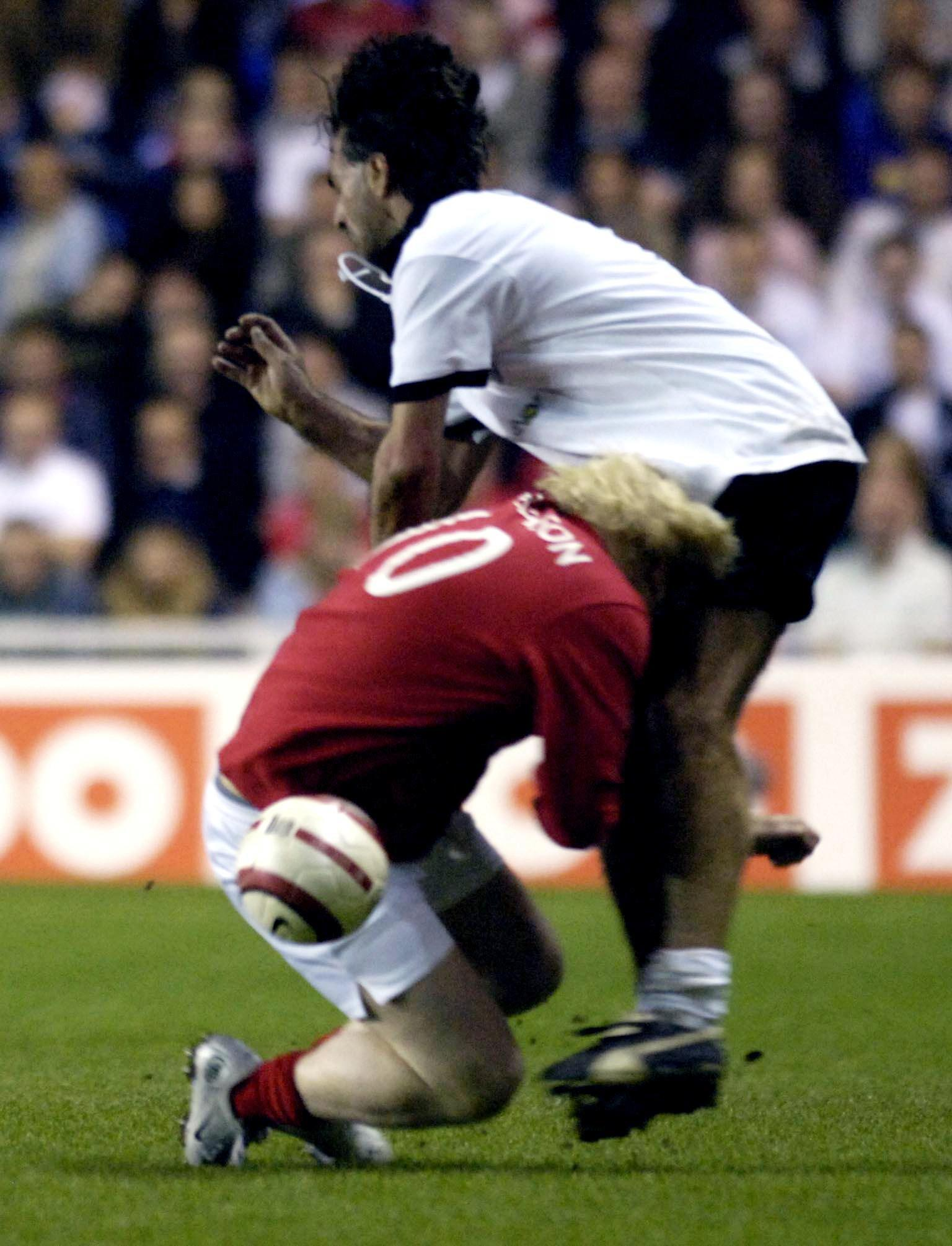 England's Boris Johnson (L) tackles Germany's Maurizio Gaudino during the Legends match at the Madejski Stadium in Reading.
