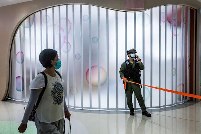 A riot police officer stands guard after a protest by district councillors at a mall in Yuen Long in Hong Kong on July 19, 2020, against a mob attack by suspected triad gang members inside the Yuen Long train station on July 21, 2019. (Photo by ISAAC LAWRENCE / AFP) (Photo by ISAAC LAWRENCE/AFP via Getty Images)