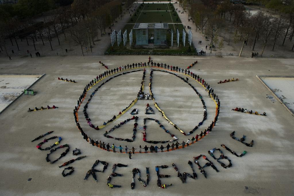 "People make the ""Pray for Paris"" sign along with the slogan ""100 percent renewable"" in Paris on December 6, 2015 on the sidelines of the COP21 climate change conference (AFP Photo/Martin Bureau)"