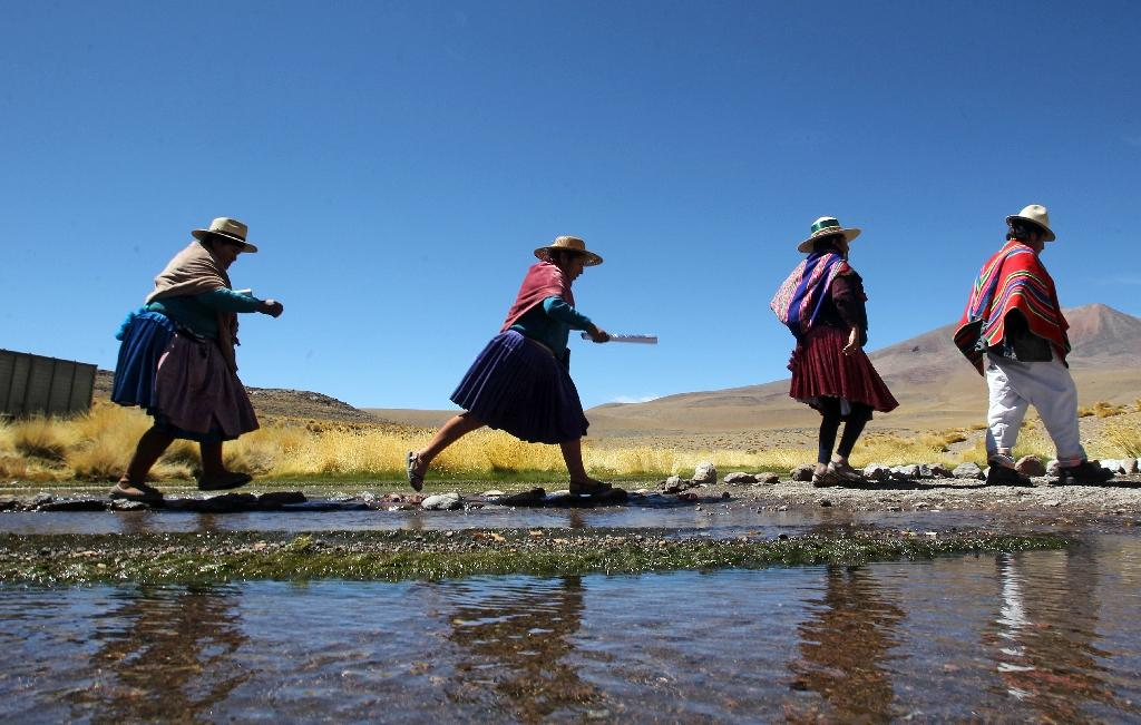 Aymara indigenous people walk along the Silala springs, in southwestern Bolivia, 4 km away from the border with Chile, on March 29, 2016