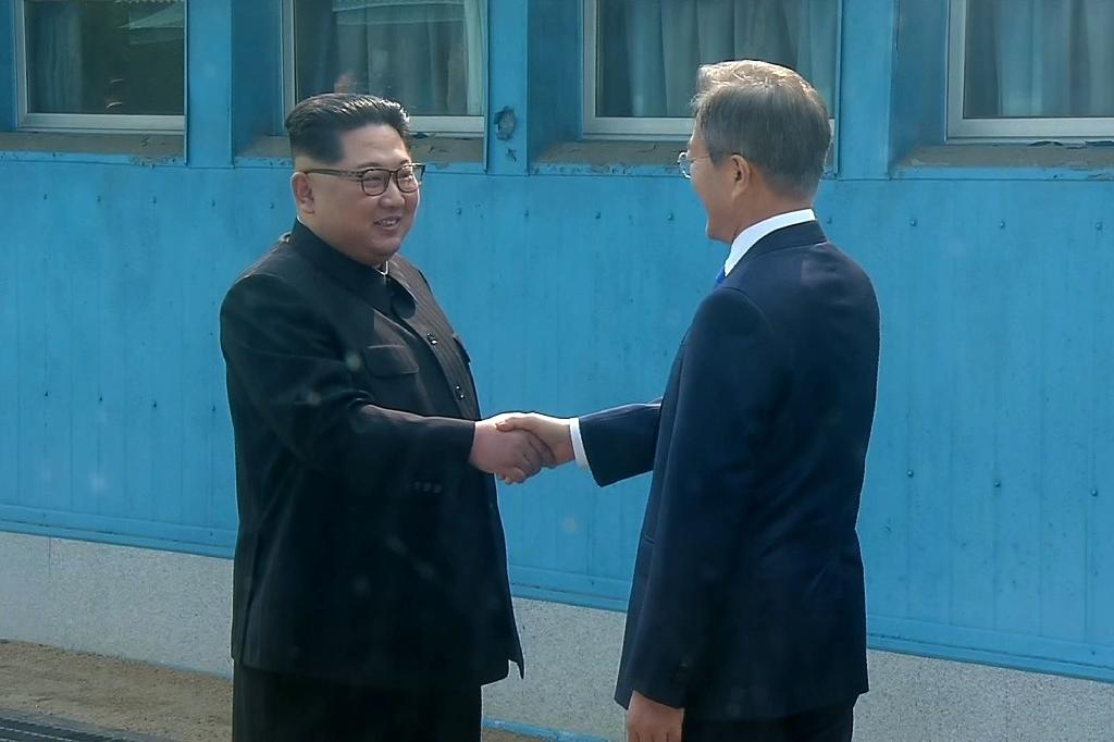 North Korea's leader Kim Jong Un and South Korea's President Moon Jae-in made history when they reached across the Military Demarcation Line (AFP Photo/KOREAN BROADCASTING SYSTEM)