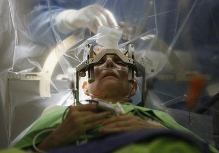 A woman lies on an operating table during a brain surgery at the National Neurology Institute in Budapest