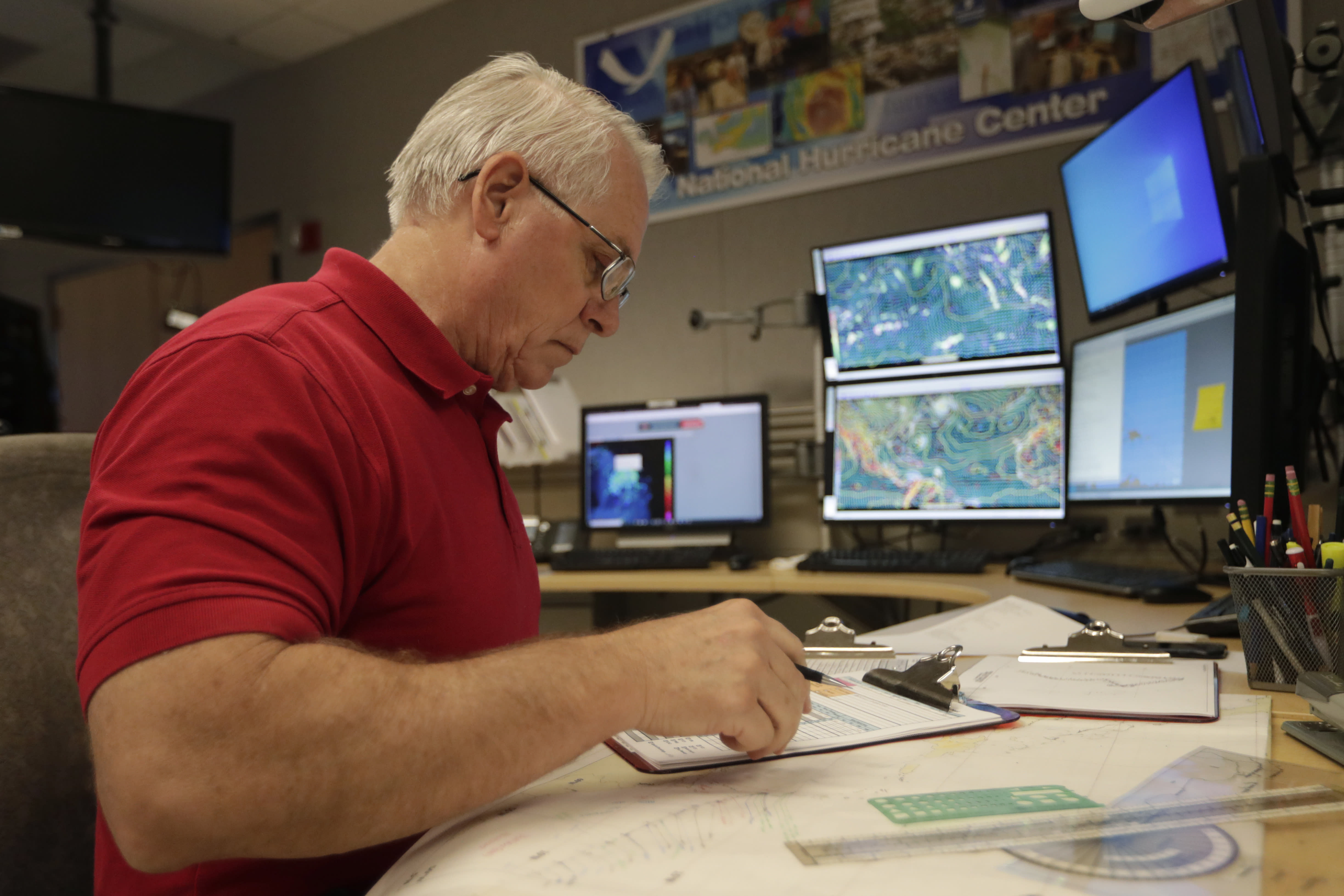 Senior hurricane specialist Stacy Stewart monitors the progress of Tropical Storm Dorian at the National Hurricane Center, Tuesday, Aug. 27, 2019, in Miami. (AP Photo/Lynne Sladky)
