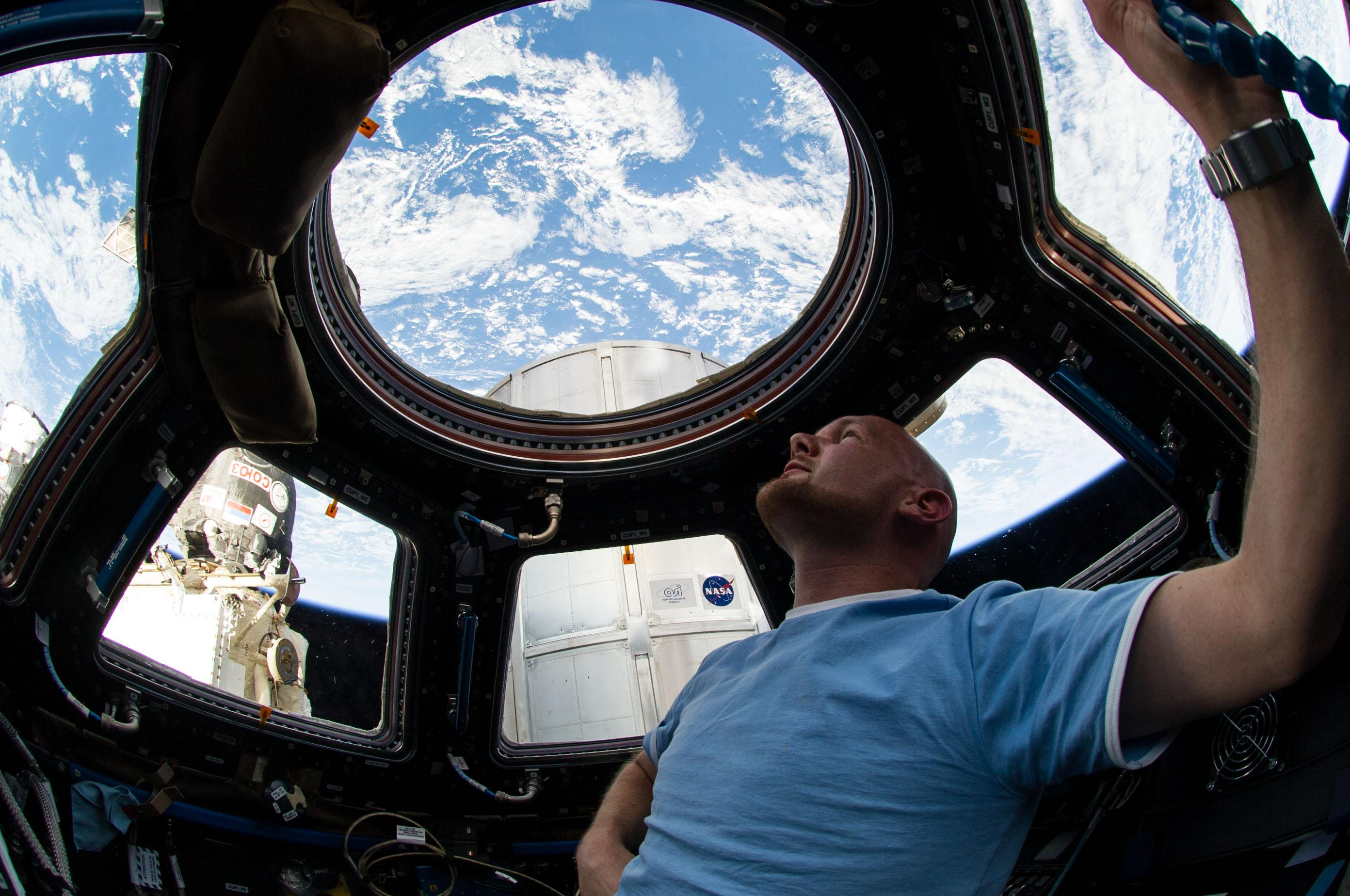 European Space Agency astronaut Alexander Gerst, Expedition 40 flight engineer, enjoys the view of Earth from the windows in the Cupola of the International Space Station. A blue and white part of Earth is visible through the windows.