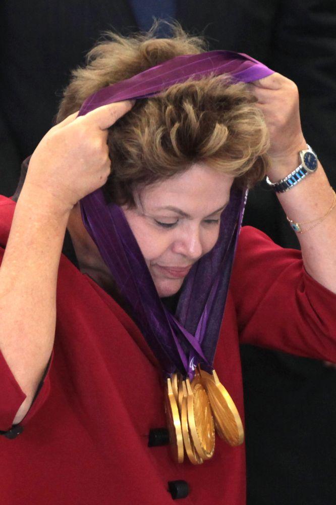 En esta foto del jueves 13 de septiembre de 2012, la presidenta brasileña Dilma Rousseff se quita las medallas que conquistó el nadador paralímpico de su país Daniel Farias Dias, durante una ceremonia en Brasilia, en la que también se reveló el plan de su país para preparar a sus atletas que competirán en Río 2016  (AP Foto/Eraldo Peres)
