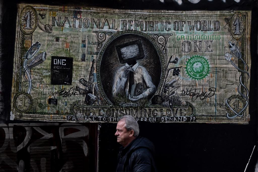 A man passes by a graffiti depicting a modified US dollar in the center of Athens on March 18, 2015 (AFP Photo/Aris Messinis)
