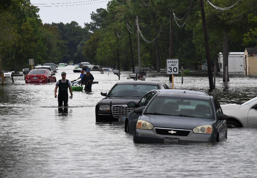 Local residents wade through flooded streets after Hurricane Harvey caused heavy flooding in Crosby, Texas on August 30, 2017
