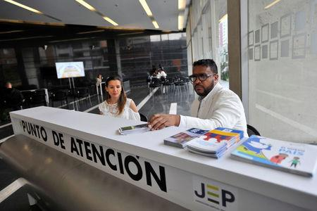 Officials of the Special Jurisdiction for Peace (JEP) tribunal, founded under a 2016 peace deal between the government and Revolutionary Armed Forces of Colombia (FARC) rebels, sit at an information booth, in Bogota, Colombia March 15, 2018. REUTERS/Carlos Julio Martinez NO RESALES. NO ARCHIVES.