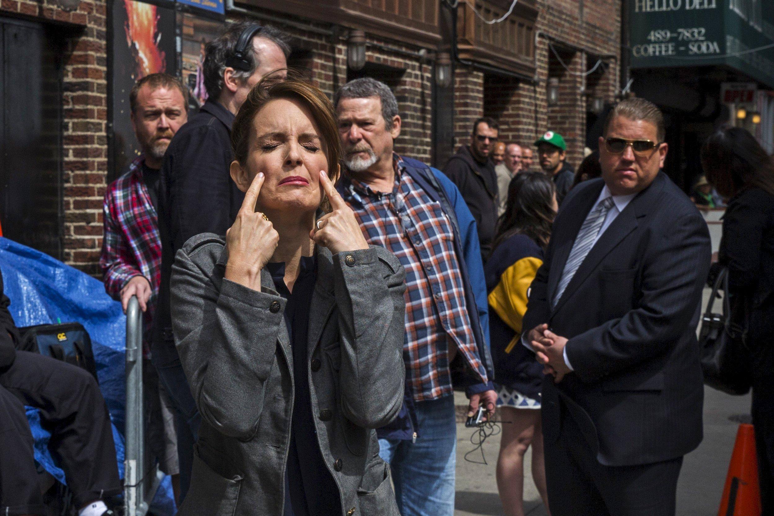 """Comedian Tina Fey pretends to cry as she arrives at Ed Sullivan Theater in Manhattan as David Letterman prepares for the taping of tonight's final edition of """"The Late Show"""" in New York May 20, 2015. REUTERS/Lucas Jackson"""
