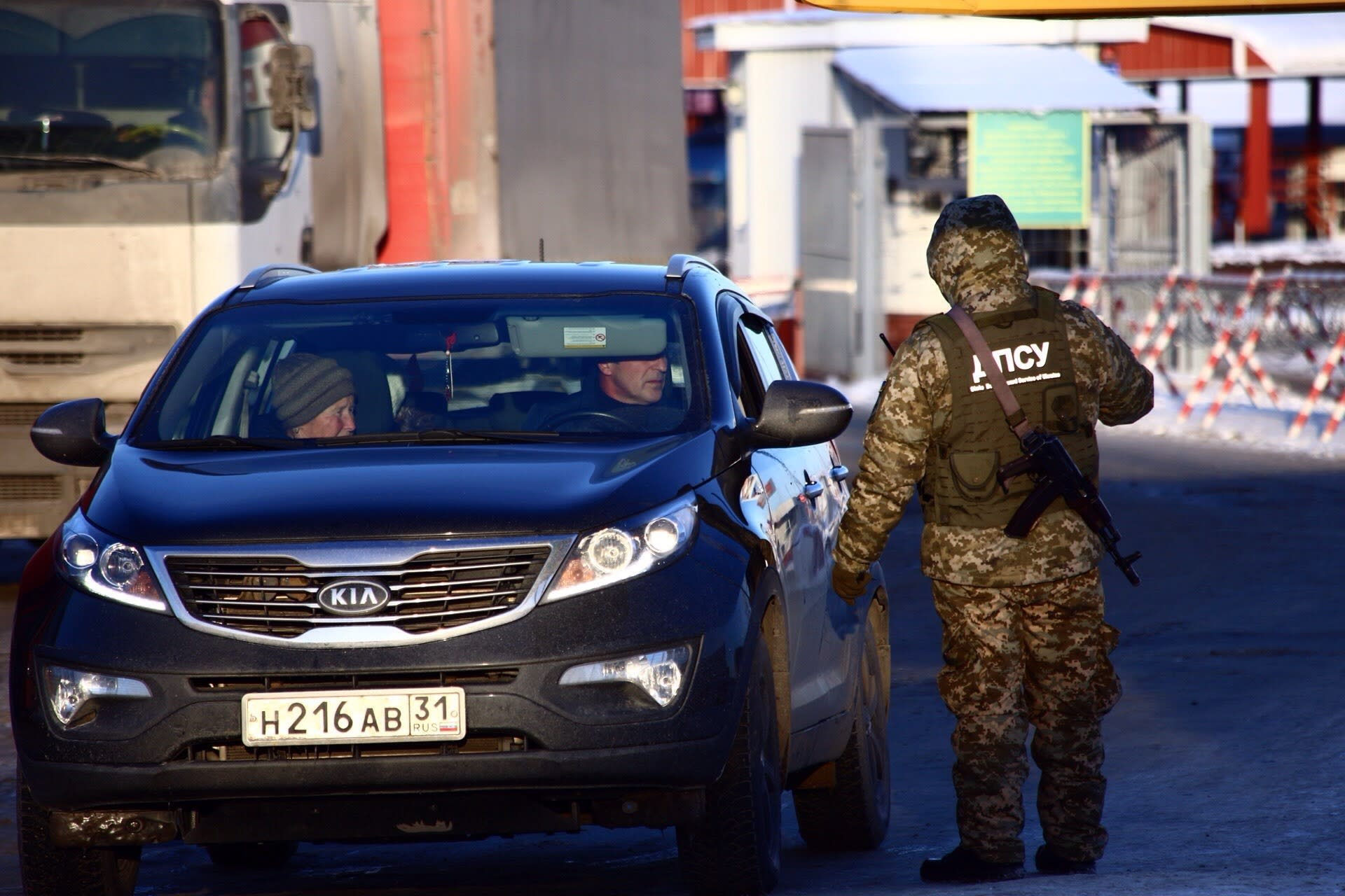 A Ukrainian border guard speaks to a driver of a car from Russia at the checkpoint at the border with Russia in Hoptivka, Ukraine, Friday, Nov. 30, 2018. Ukrainian officials announced earlier on Friday that all Russian men aged between 16 and 60 will be barred from entering Ukraine for the duration of the 30-day-long martial law. (AP Photo/Pavlo Pakhomenko)