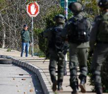 Israel hunts Palestinian gunmen, raids official news agency