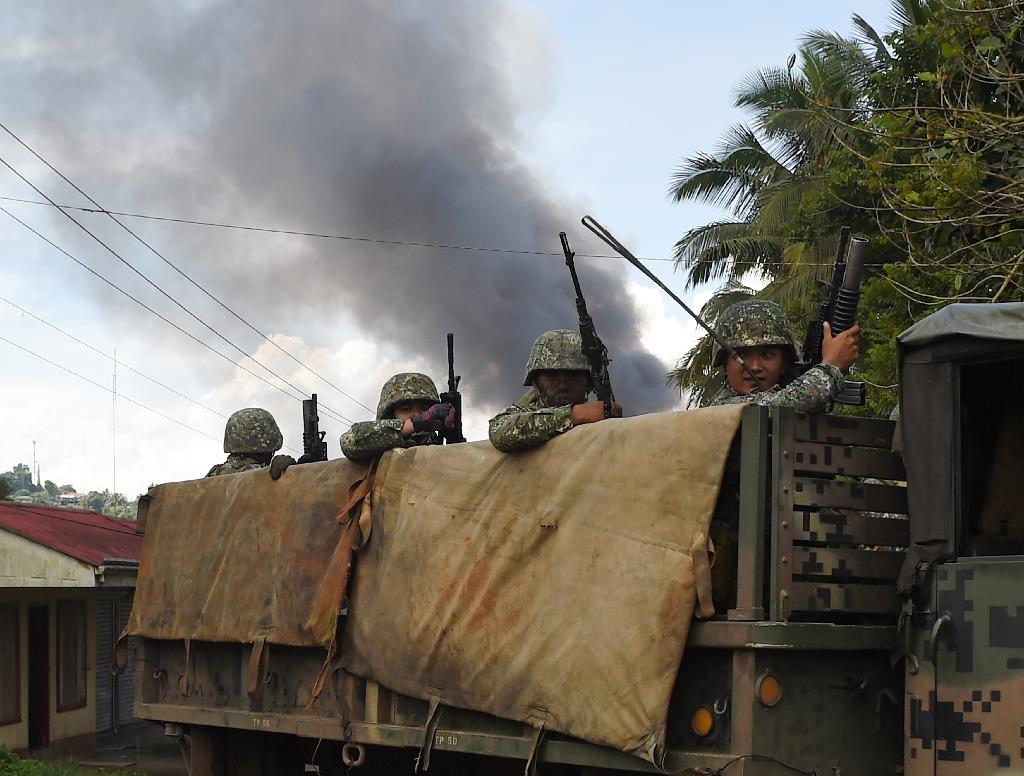 Philippine Marines aboard their truck drive past as smoke billows after military helicopters fired rockets at militant positions in Marawi on the southern island of Mindanao (AFP Photo/TED ALJIBE)