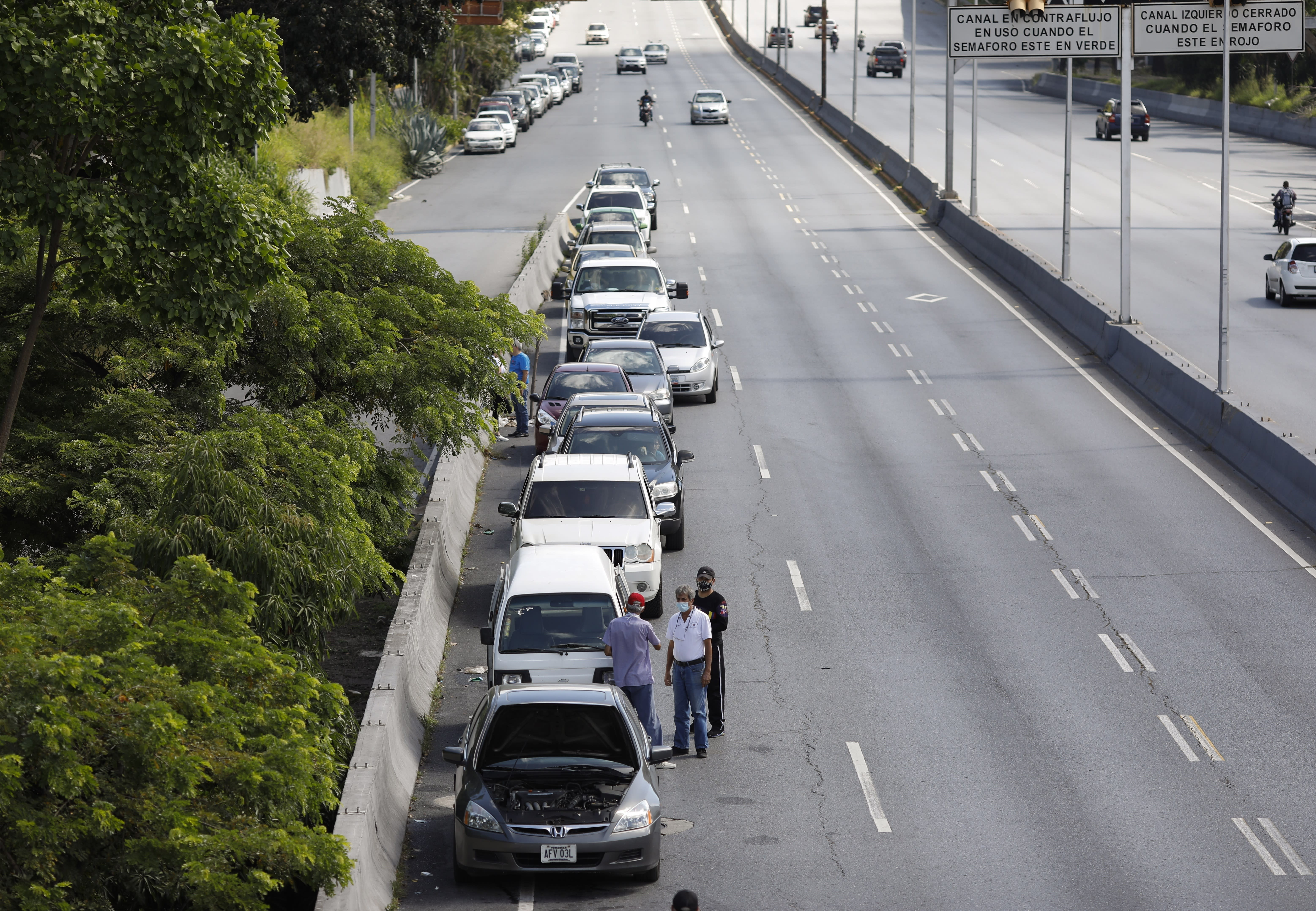 Men stand alongside vehicles lined up to enter a gas station during a nation-side fuel crunch, in Caracas, Venezuela, Wednesday, Sept 30, 2020. (AP Photo/Ariana Cubillos)