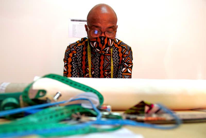 A tailor works at the workshop of fashion designer Sophie Zinga