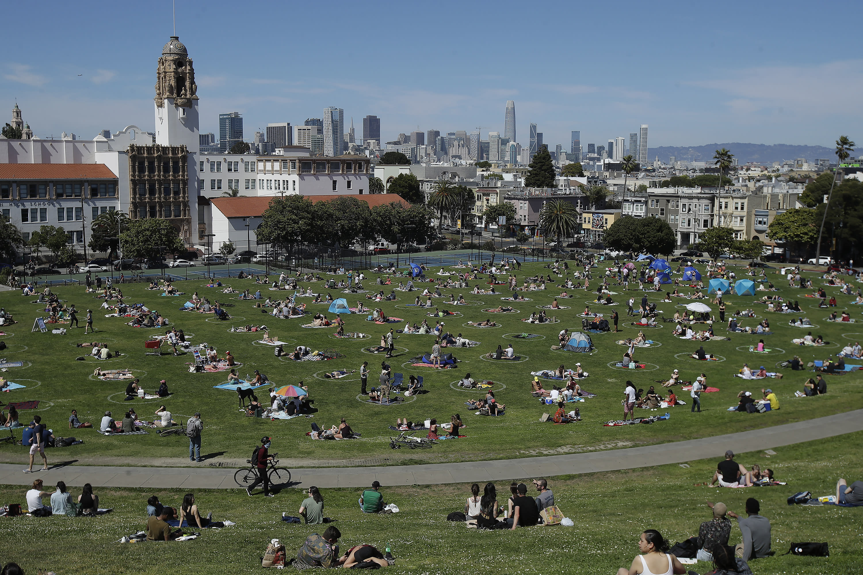 FILE - In this Sunday, May 24, 2020, file photo, visitors set up inside circles designed to help prevent the spread of the coronavirus by encouraging social distancing at Dolores Park in San Francisco. The city said it would continue to delay the reopening of some businesses because of a surge of infections in the city, where the positive case rate per 100,000 has increased to nearly 8%. The goal is to keep it at around 2%, said Dr. Grant Colfax, director of public health. San Francisco's population of nearly 900,000 people has fared remarkably well during the pandemic, with a total of 4,696 cases and 50 deaths, as of Wednesday, July 15, 2020. (AP Photo/Jeff Chiu, File)