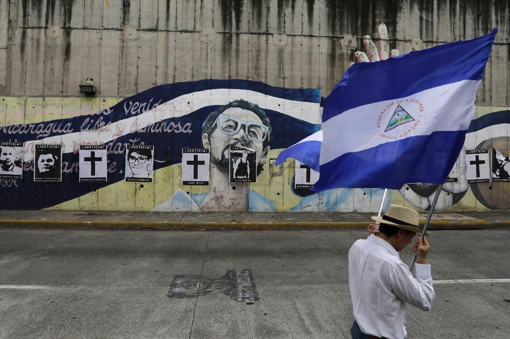 A Nicaraguan opposition demonstrator holds a national flag, as he takes part in a nationwide march called 'United we are a volcano' in Managua on July 12 (AFP Photo/INTI OCON)