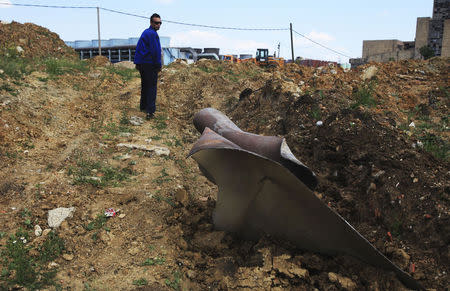 A man looks at a piece of metal after the explosion of a hydrogen tank in Kosova A power plant in Obilic, near Pristina, June 6, 2014. REUTERS/Hazir Reka