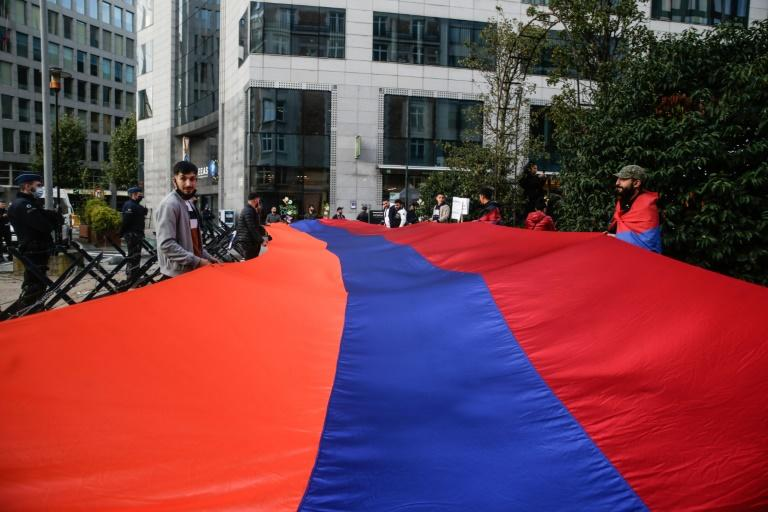 People hold a giant Armenian flag during a rally in support of Armenia and against the war in the Nagorno Karabach region during the Special European Summit in Brussels