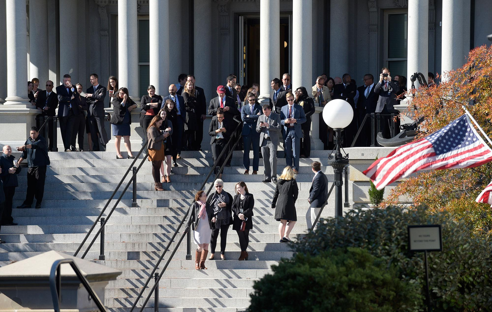 <p>People stand on the steps of the Eisenhower Executive Office Building, next to the White House, in Washington, Thursday, Nov. 10, 2016, as they wait for the arrival of President-elect Donald Trump for his meeting with President Obama. (AP Photo/Susan Walsh) </p>