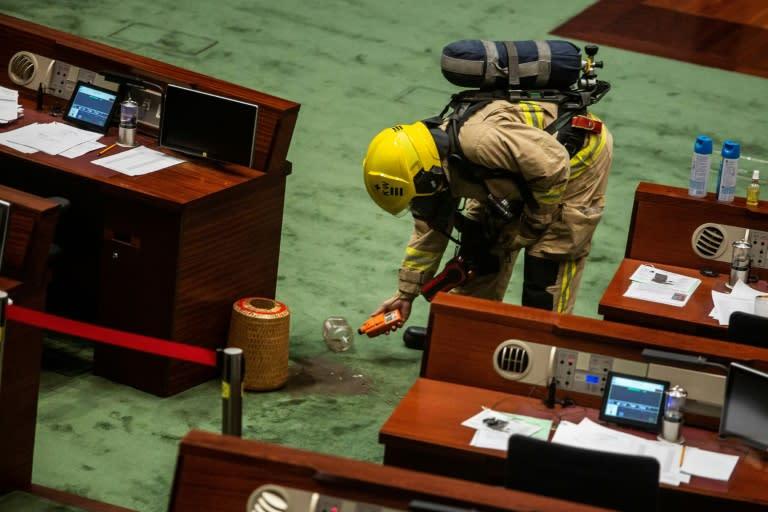 A fireman inspects a jar of fertiliser thrown inside Hong Kong's legislature (AFP Photo/ISAAC LAWRENCE)