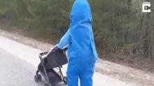 Mutter geht mit Baby im Hai-Kostüm spazieren