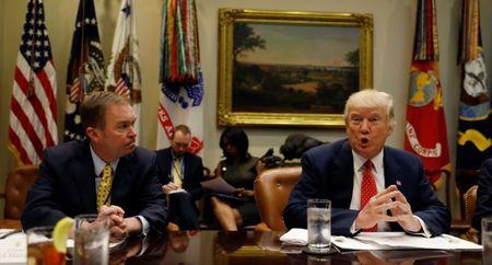 """Director of the Office of Management and Budget Mick Mulvaney (L) listens to U.S. President Donald Trump speak during a """"strategic initiatives"""" lunch at the White House in Washington, U.S., February 22, 2017. REUTERS/Kevin Lamarque"""