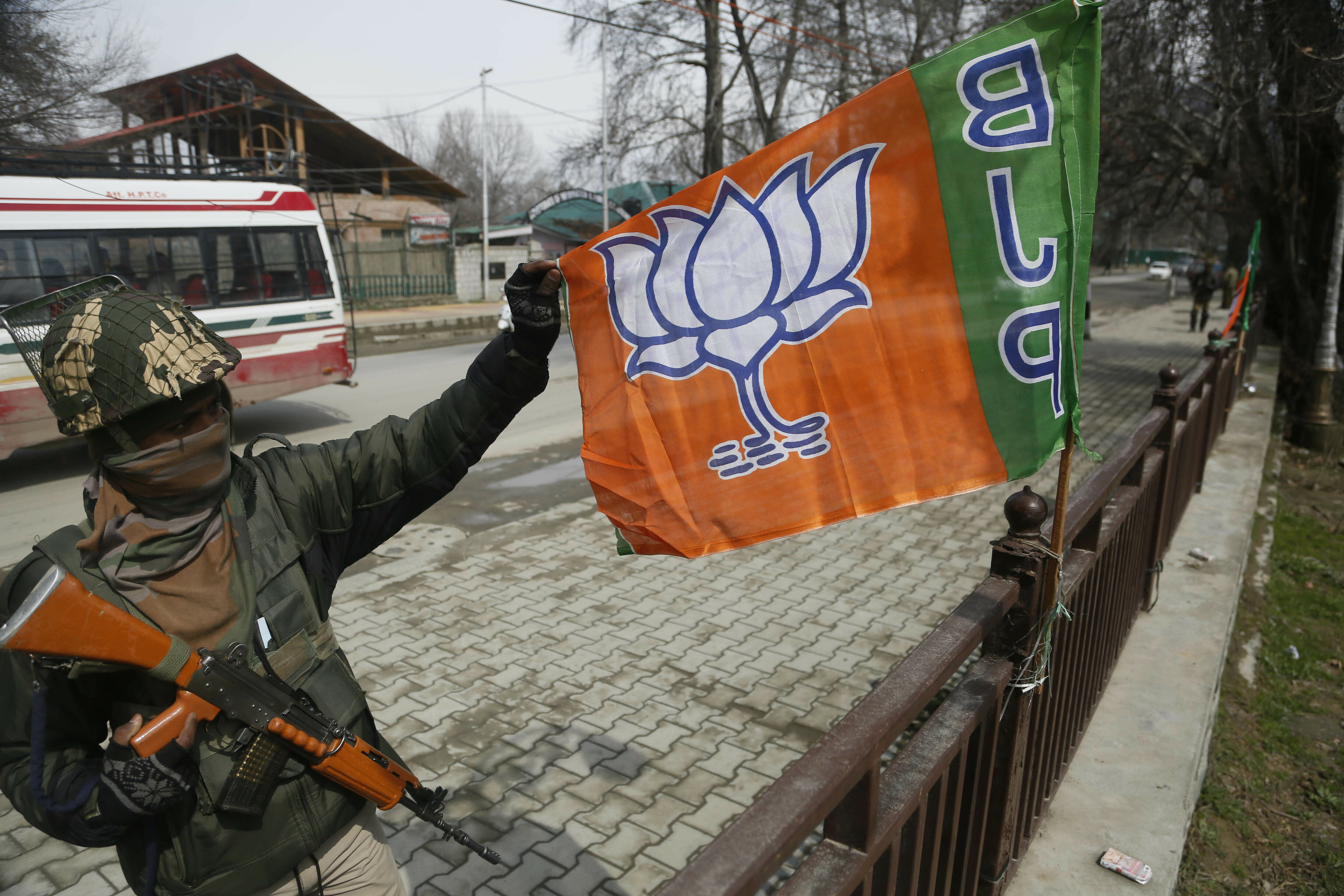 "FILE - In this Thursday, March 14, 2019, file photo, an Indian paramilitary soldier holds a flag of India's ruling Bharatiya Janata Party (BJP) as he stands guard during a meeting of the party ahead of the upcoming elections in Srinagar, Indian controlled Kashmir. Indian Prime Minister Narendra Modi has promised early elections in the Indian-controlled portion of Kashmir days after stripping it of statehood and turning it into a federally administered territory. In an address to the nation late Thursday, Aug. 8, Modi said the change in Kashmir's set-up will help free the disputed region of ""terrorism and separatism"" and put it on a path of development. (AP Photo/Mukhtar Khan, File)"