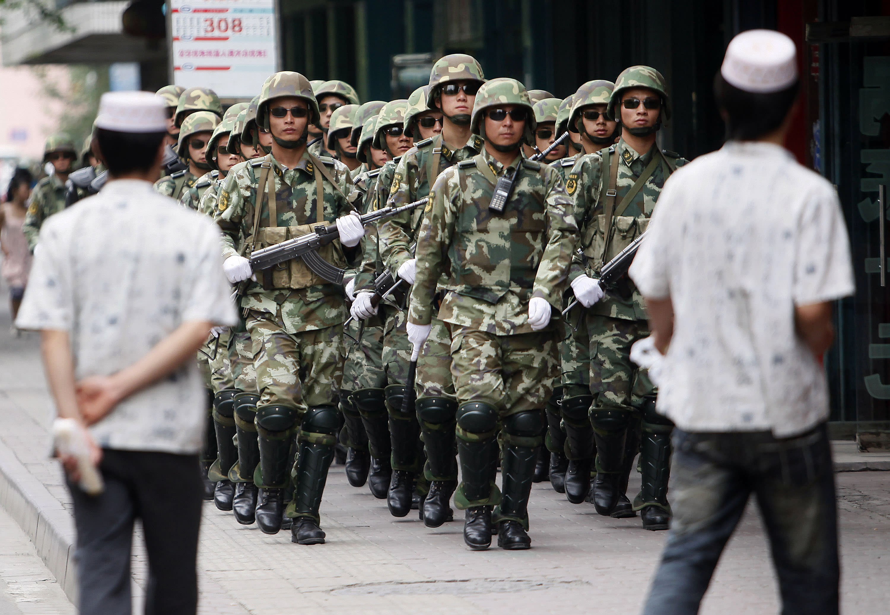 """FILE - In this Monday, July 13, 2009, file photo, paramilitary police officers patrol in the aftermath of riots as Uighur men walk by in Urumqi, western China's Xinjiang province. Analysts say the Urumqi riots in 2009 set in motion the harsh security measures now in place across Xinjiang, where about 1 million Uighurs, Kazakhs and other Muslims are estimated to be held in heavily-guarded internment camps _ also called """"re-education"""" camps _ which the Chinese government describes as vocational training centers. (AP Photo/Eugene Hoshiko, File)"""