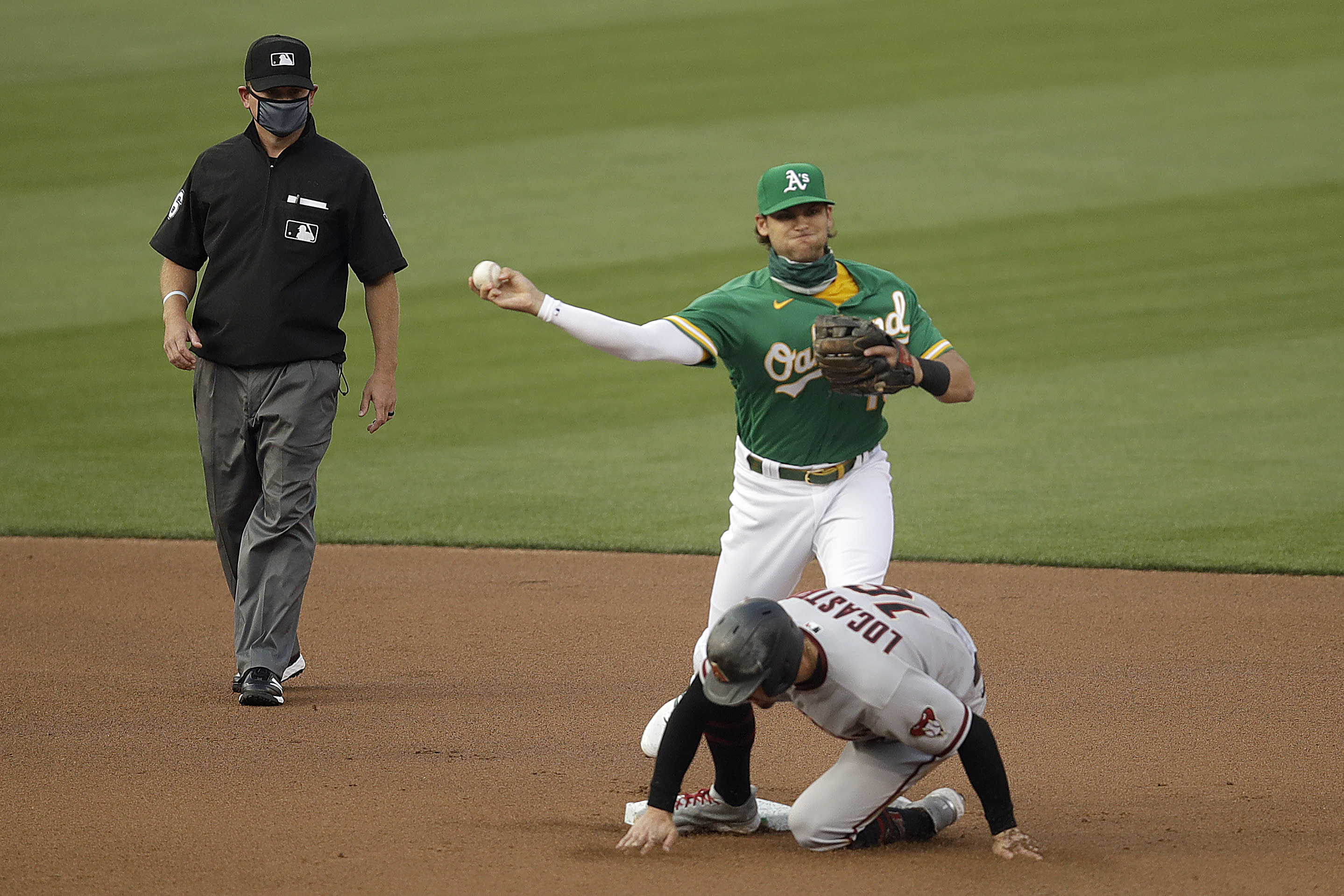 Oakland Athletics' Chad Pinder throws over Arizona Diamondbacks' Tim Locastro to complete a double play in the first inning of a baseball game Thursday, Aug. 20, 2020, in Oakland, Calif. Arizona's Ketel Marte was out at first base. (AP Photo/Ben Margot)