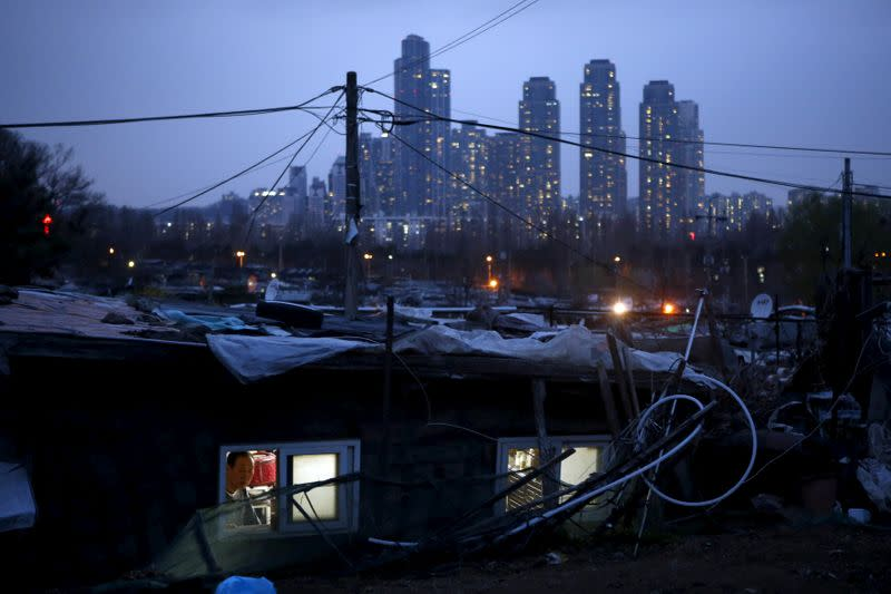FILE PHOTO: A man looks out from his shack as a luxury high-rise apartment complex is seen in the background at Guryong village in Seoul