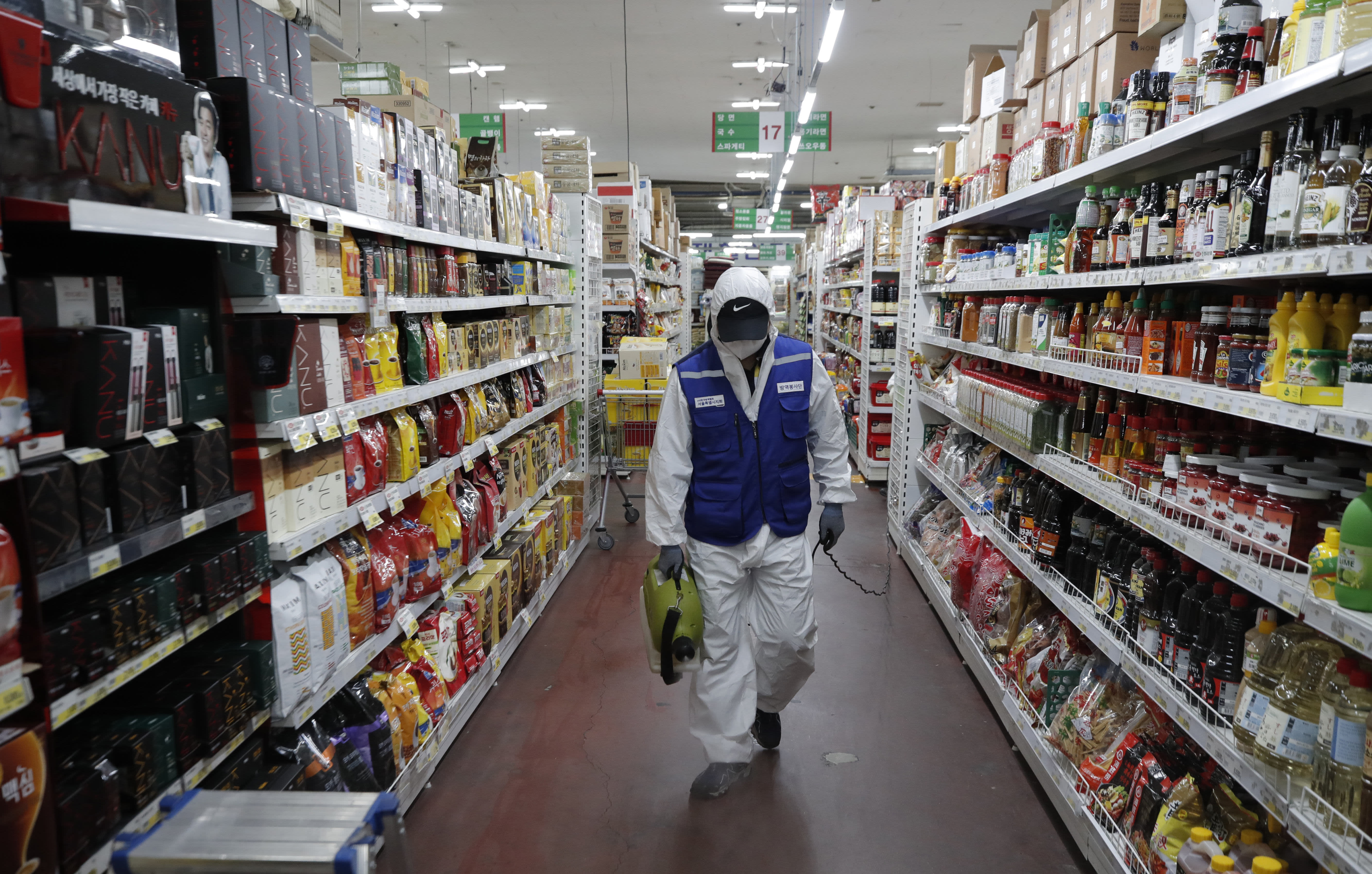 A worker wearing a protective suit sprays disinfectant as a precaution against the COVID-19 at a market in Seoul, South Korea, Thursday, Feb. 27, 2020. (AP Photo/Lee Jin-man)