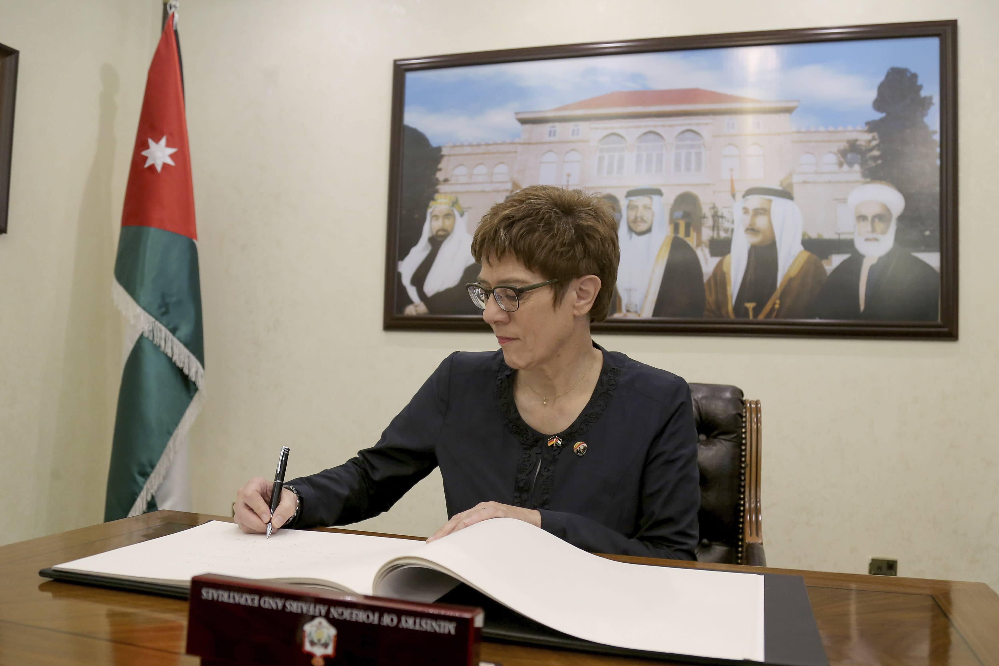 German Defense Minister Annegret Kramp-Karrenbauer signs the guestbook of the Foreign Minister of Jordan, in Amman, Jordan, Monday, August 19, 2019. It was Kramp-Karrenbauer's first trip abroad as Defense Minister. (AP Photo/Raad Adayleh)