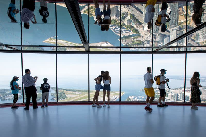 Visitors view panoramic city scenes from the CN Tower in Toronto