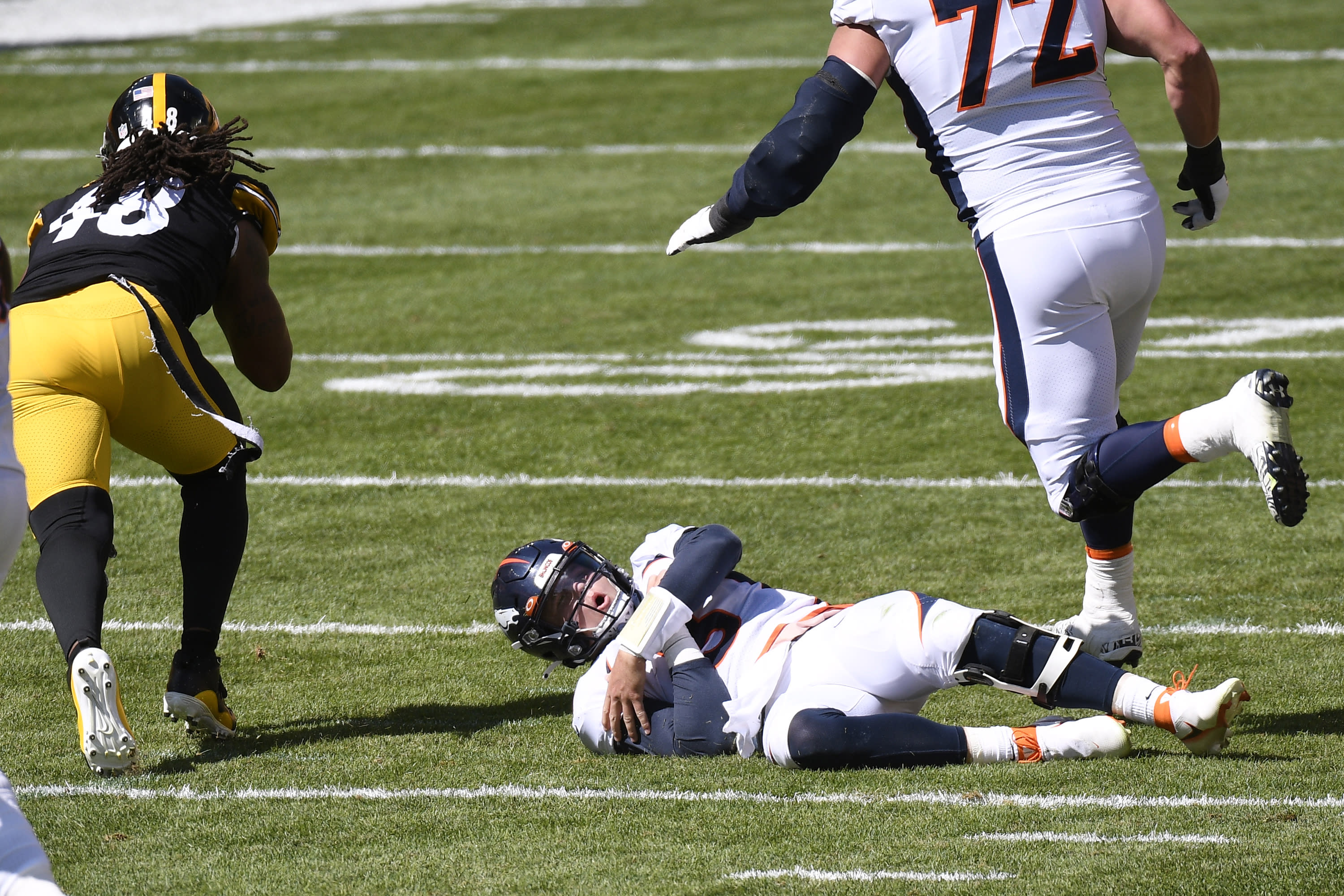 Denver Broncos quarterback Drew Lock (3) holds his arm after being injured while fumbling the ball during the first half of an NFL football game against the Pittsburgh Steelers, Sunday, Sept. 20, 2020, in Pittsburgh. (AP Photo/Keith Srakocic)