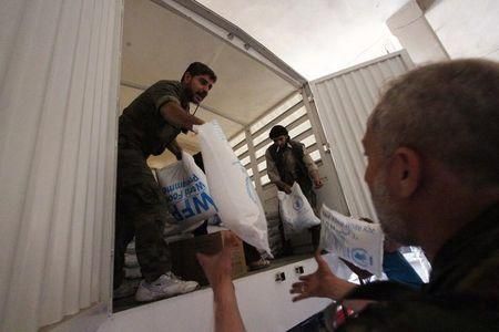 People unpack humanitarian aid in a warehouse in Ghouta