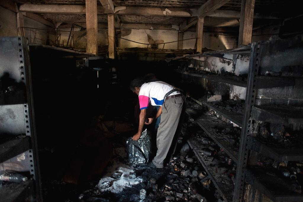 A man looks for goods amid the rubble of a burnt market in Ciudad Bolivar on December 19, 2016 (AFP Photo/MANAURE QUINTERO)