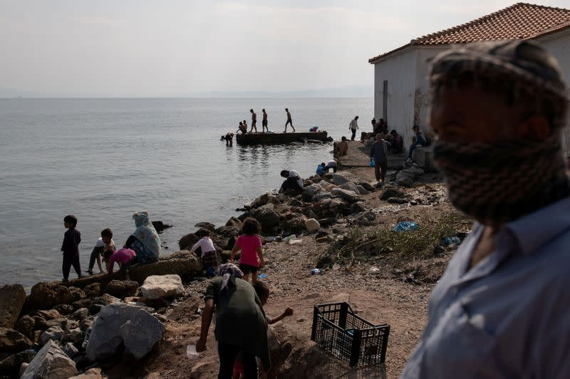 Refugees and migrants from the destroyed Moria camp are seen on a beach near a new temporary camp, on the island of Lesbos