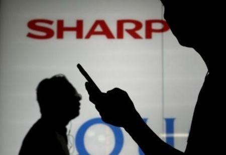 File photo of a man using his mobile phone walking past a logo of Sharp Corp outside an electronics shop in Tokyo