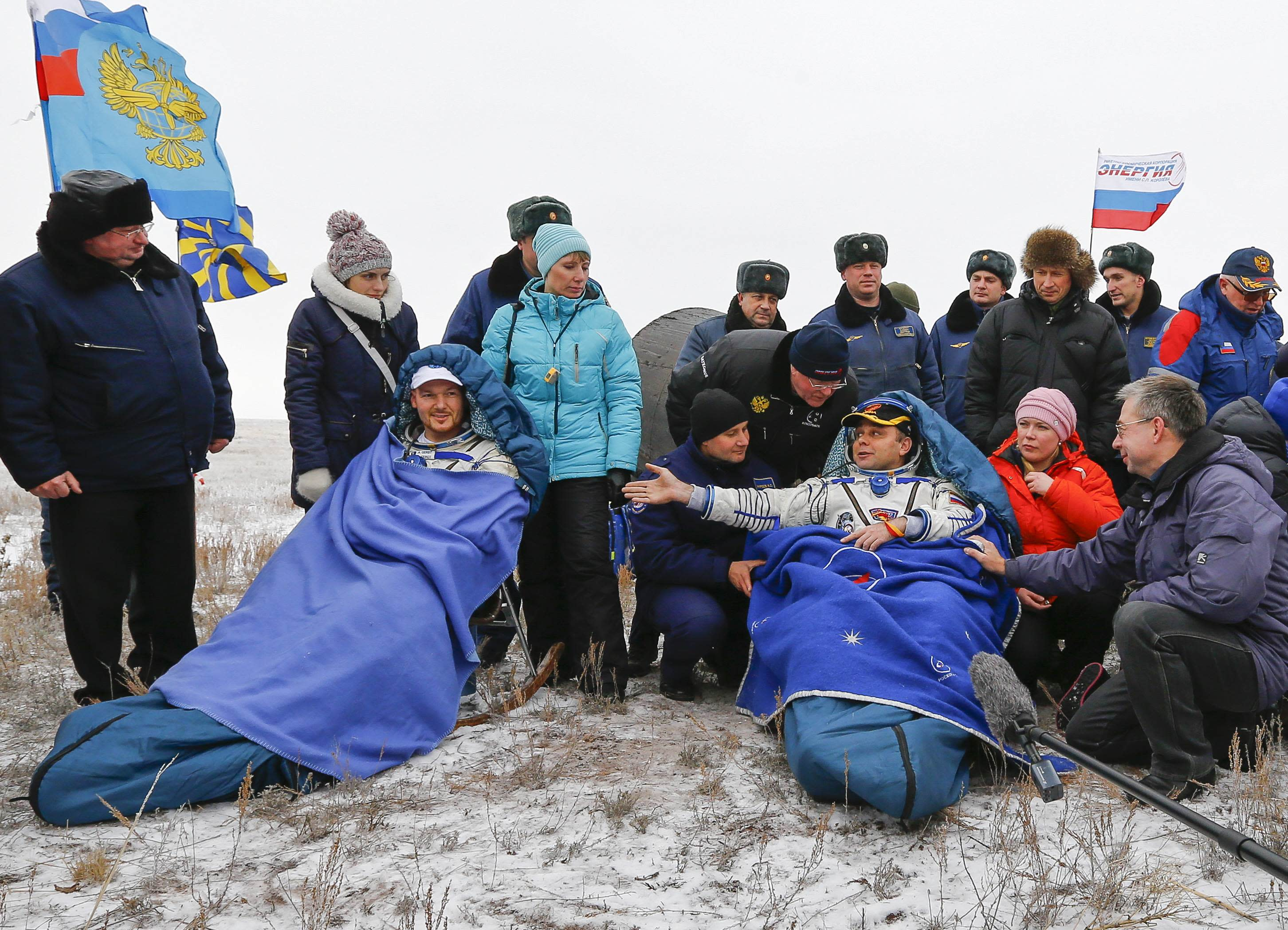 REFILE - CLARIFYING DATE OF LANDING IN SECOND SENTENCE International Space Station (ISS) crew member Maxim Suraev of Russia (R) gestures to his teammate Alexander Gerst of Germany after landing in a remote area near the town of Arkalyk in northern Kazakhstan November 10, 2014. Veteran Russian cosmonaut Suraev and two International Space Station crewmates, NASA's Reid Wiseman from the United States and Gerst from Germany, returned safely to Earth on Monday with a parachute landing of their Soyuz capsule in Kazakhstan, ending 5-1/2 months in orbit. REUTERS/Shamil Zhumatov (KAZAKHSTAN - Tags: SCIENCE TECHNOLOGY)