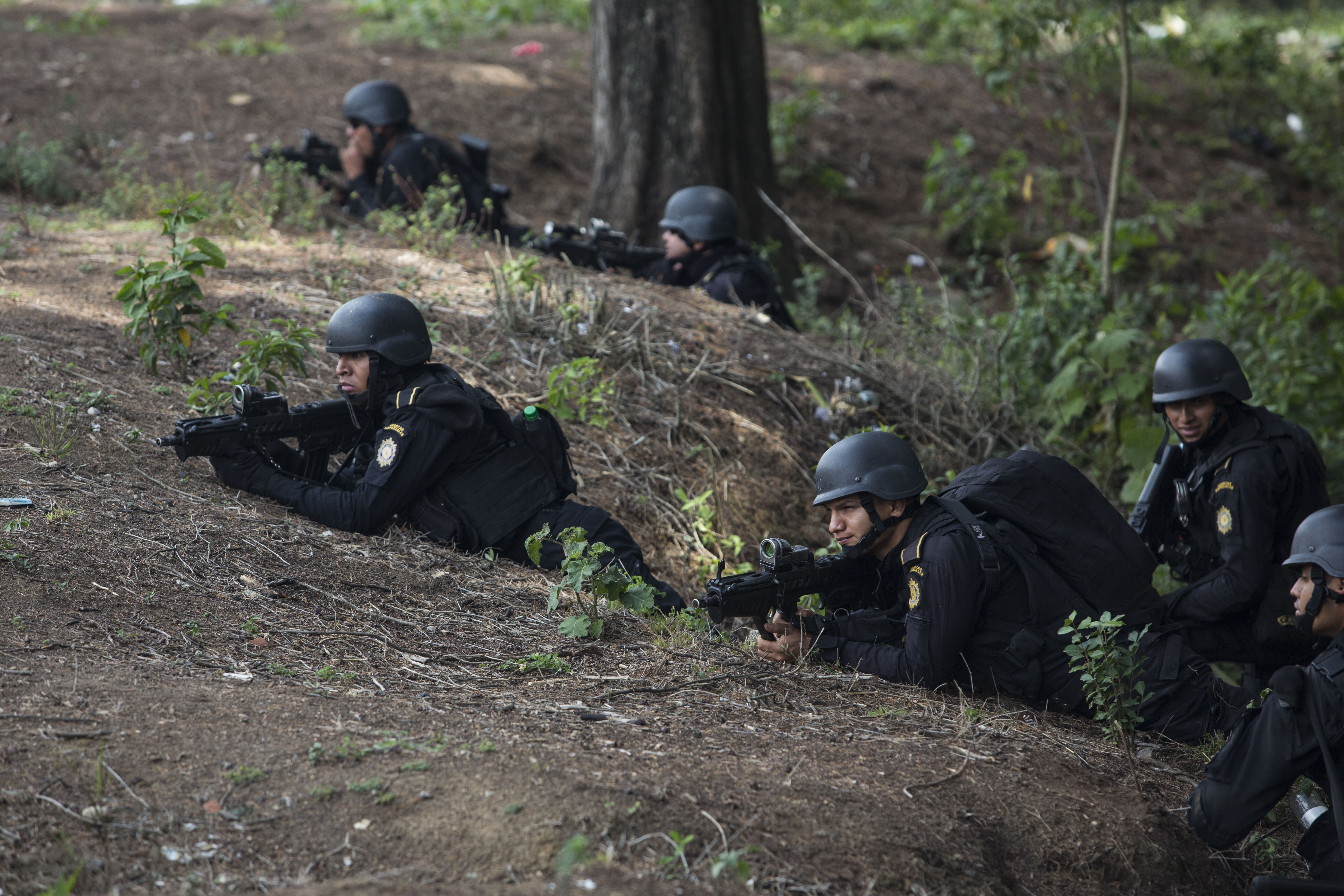 Special task force police take position outside the Pavon Rehabilitation Model Farm after a shooting inside the jail in Fraijanes, Guatemala, Tuesday, May 7, 2019. At least three people were killed and 10 people were wounded in the shooting, authorities said. (AP Photo/Oliver De Ros)