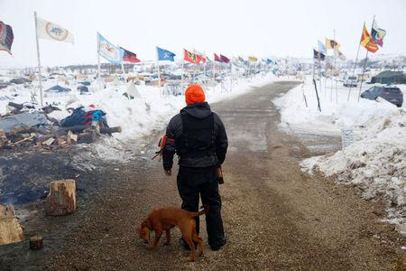 FILE PHOTO -- A security volunteer stands in the Dakota Access Pipeline protest camp near Cannon Ball, North Dakota, U.S., January 24, 2017. REUTERS/Terray Sylvester/File Photo