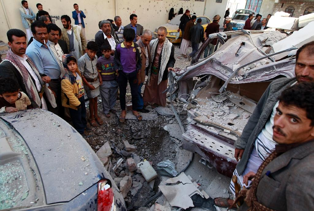 Yemenis look at destruction in the street following air strikes on the capital Sanaa, on January 5, 2016 (AFP Photo/Mohammed Huwais)