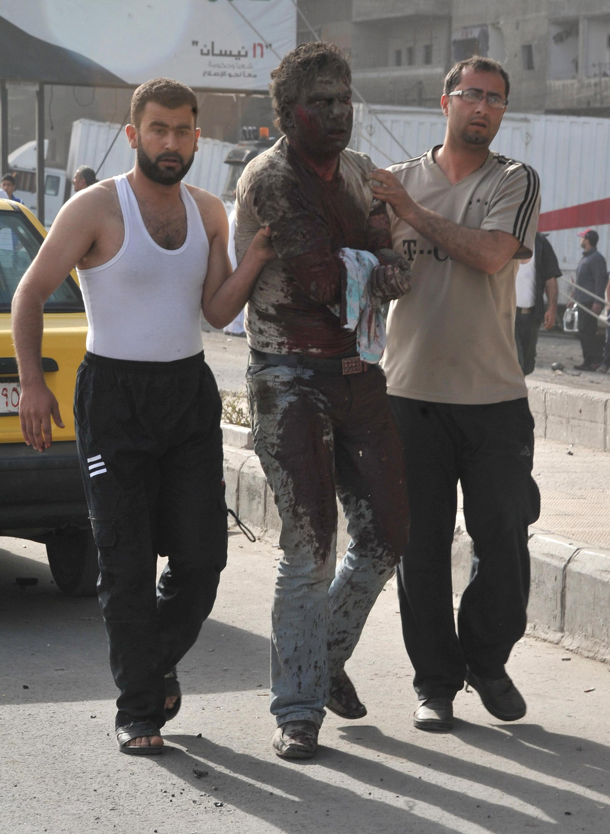 In this photo released by the Syrian official news agency SANA, Syrian citizens help an injured man after two bombs exploded, at Qazaz neighborhood in Damascus, Syria, on Thursday May 10, 2012. Two large explosions ripped through the Syrian capital Thursday, heavily damaging a military intelligence building and leaving blood and human remains in the streets. (AP Photo/SANA)