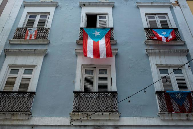 Puerto Rican National flags hang from balconies in Old San Juan, Puerto Rico on April 7, 2020. - On March 15, 2020, Puerto Rico Governor Wanda Vazquez Garced imposed a curfew shuttering non-essential businesses on the island and ordered people to stay home from 7 p.m. to 5 a.m. In addition, from March 31, she imposed even tighter measures, including requiring anyone entering a business to wear a face mask. (Photo by Ricardo ARDUENGO / AFP) (Photo by RICARDO ARDUENGO/AFP via Getty Images)
