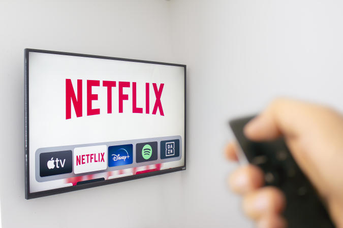 Calgary, Alberta. Canada Dec 9 2019: A Person holds an Apple TV remote using the new Netflix app with a hand. Netflix dominates Golden Globe Nominations. Illustrative