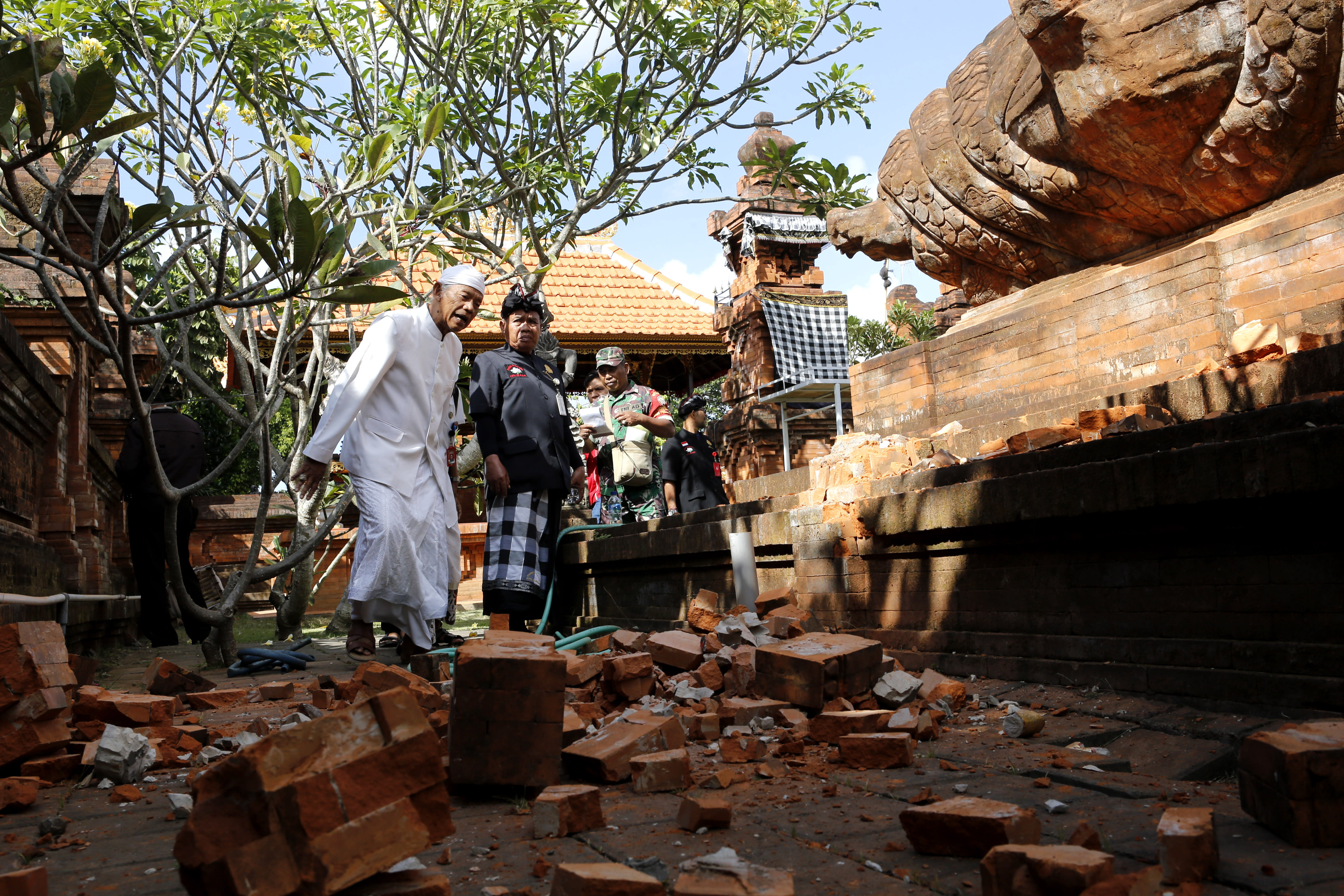 Balinese men check a damaged temple in Bali, Indonesia Tuesday, July 16, 2019. Indonesian authorities say a subsea earthquake shook Bali, Lombok and East Java on Tuesday, causing damage to homes and temples. (AP Photo/Firdia Lisnawati)