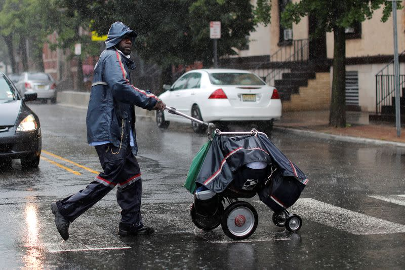 USPS Mail carrier walks through heavy rain as Tropical Storm Fay sweeps across northeastern United States in Jersey City