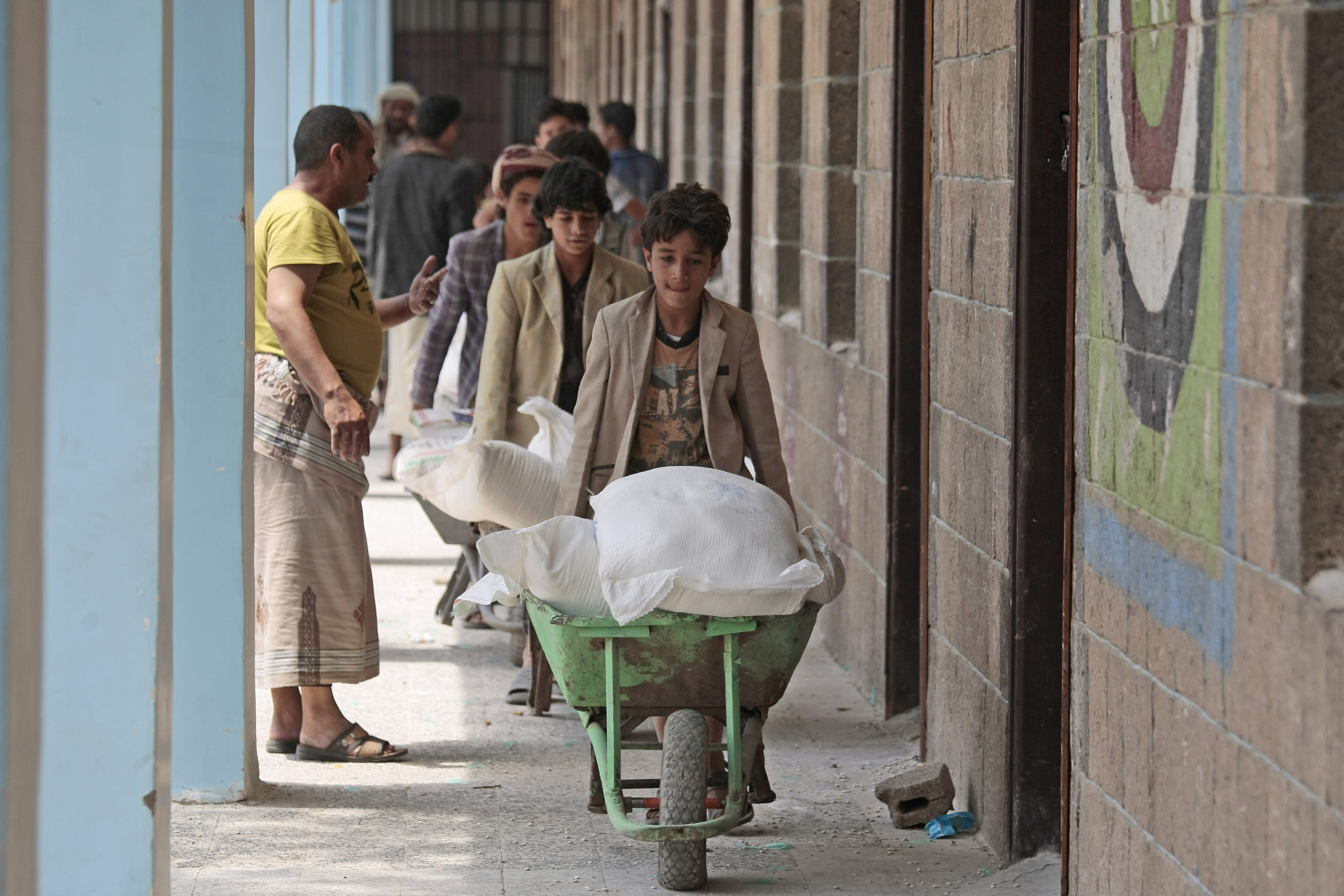 In this Aug. 25, 2019, file photo, displaced Yemenis receive food supplies provided by the World Food Programme, at a school in Sanaa, Yemen. The World Food Program chief warned Thursday, Sept. 17, 2020, that millions of people are closer to starvation because of the deadly combination of conflict, climate change and the COVID-19 pandemic and he urged donor nations and billionaires to help feed them and ensure their survival. (AP Photo/Hani Mohammed, File)